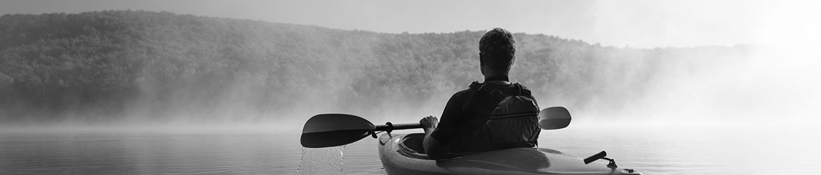 Man kayaking in misty lake