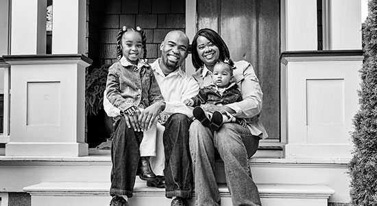 African American family sitting on porch