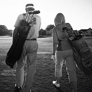 Elderly couple walking on golf course with golf bags